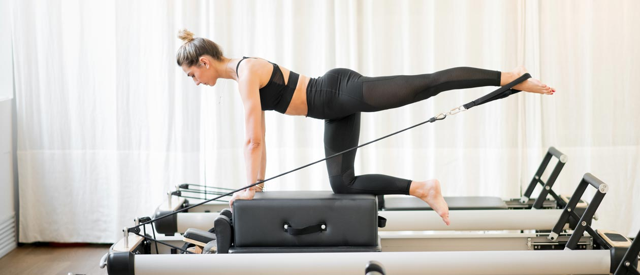 Woman exercising on a Piltaes reformer