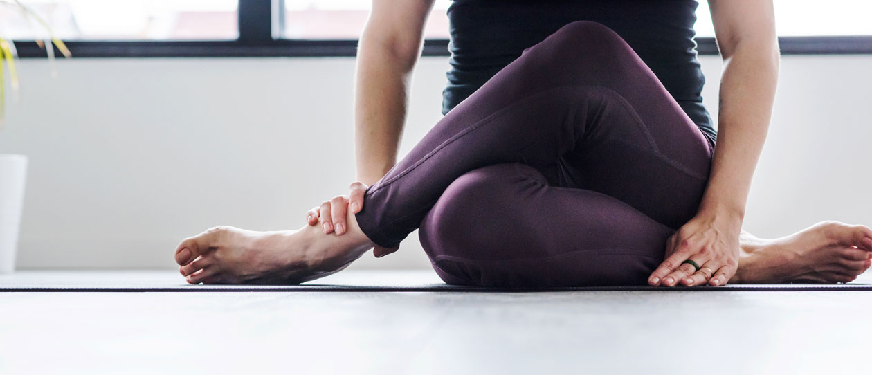 Woman stretching in a seated yoga pose to relieve delayed onset muscle soreness