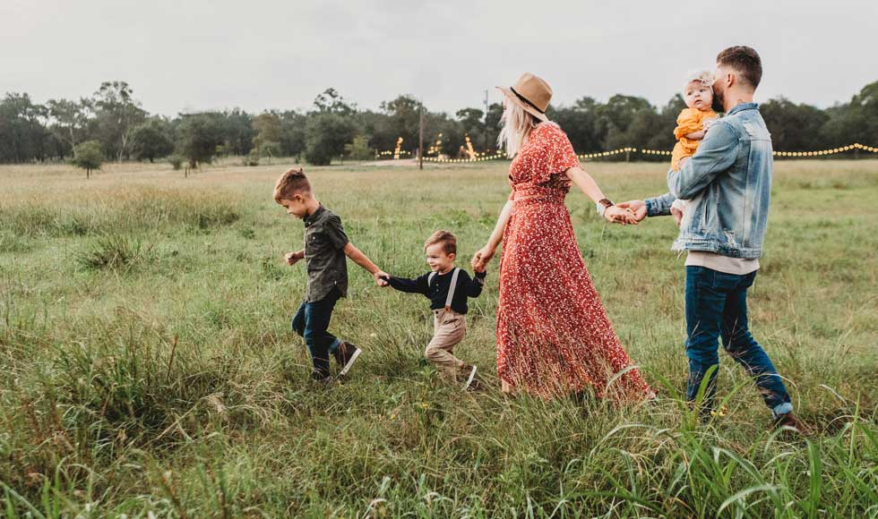 Young family of five walking through a grassy field