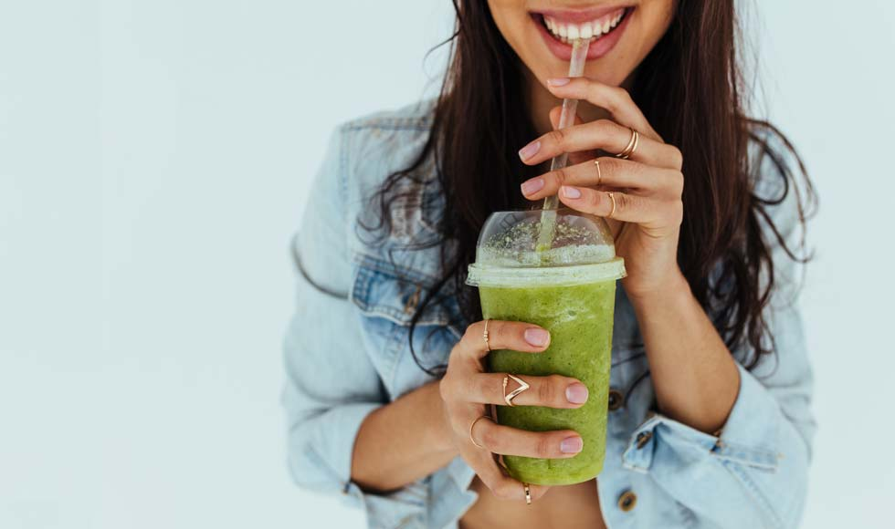Healthy young woman drinking a green juice