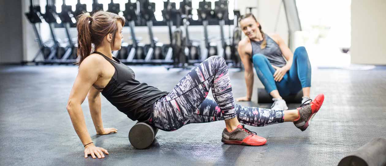 Two women using a foam roller in the gym
