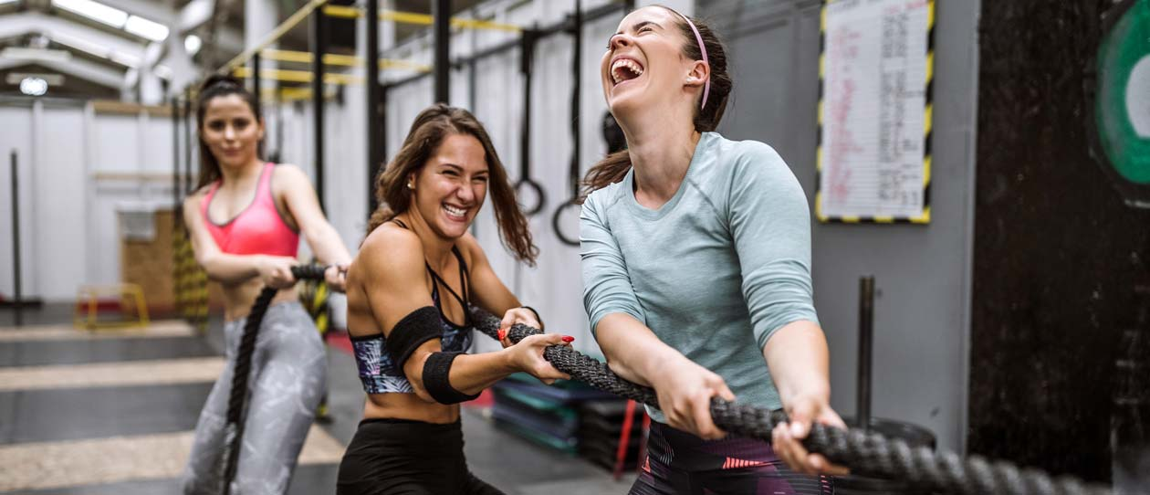 Three women laughing in a cross fit class