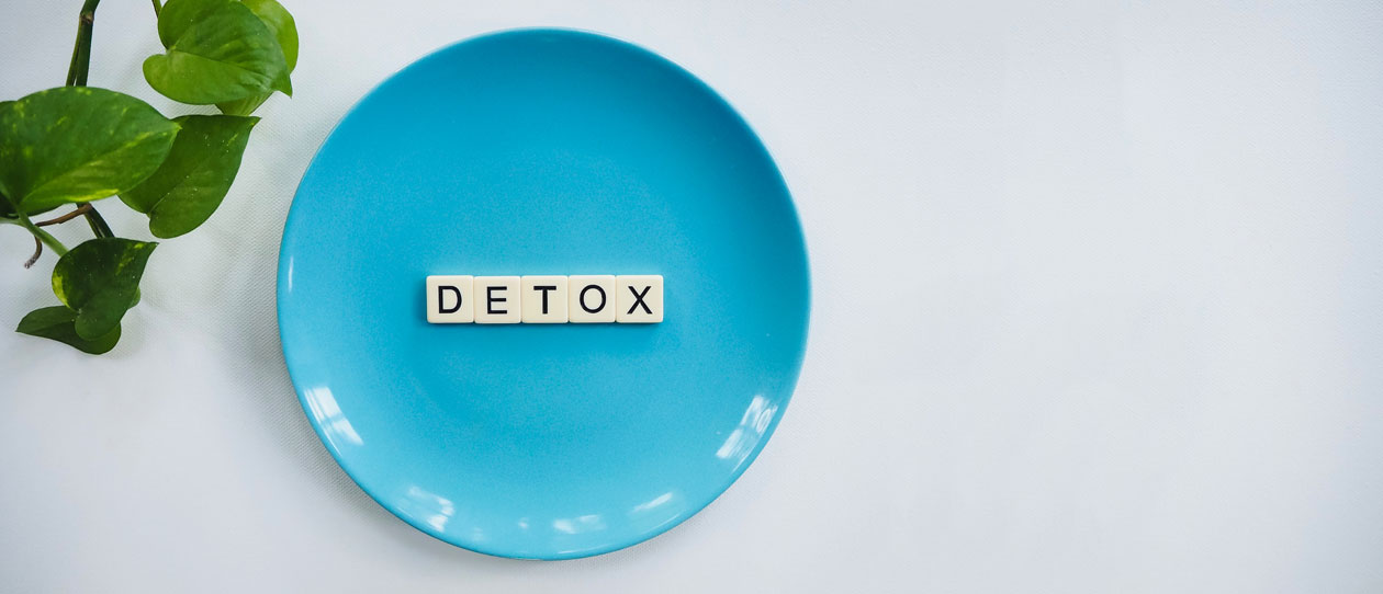 Blue plate on a white background with scrabble letters spelling detox