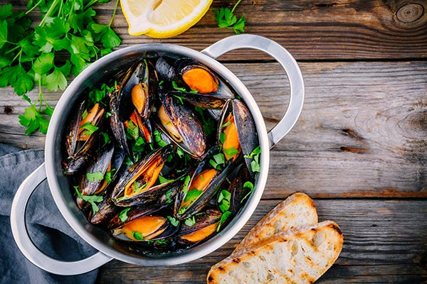Mussels in a pan with parsley, lemon and crunchy bread
