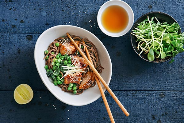 Marinated chicken with noodles, greens and lemon