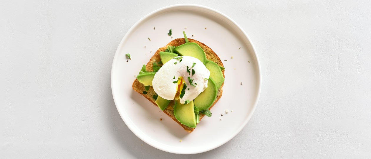 Avocado and egg on toast on a white plate