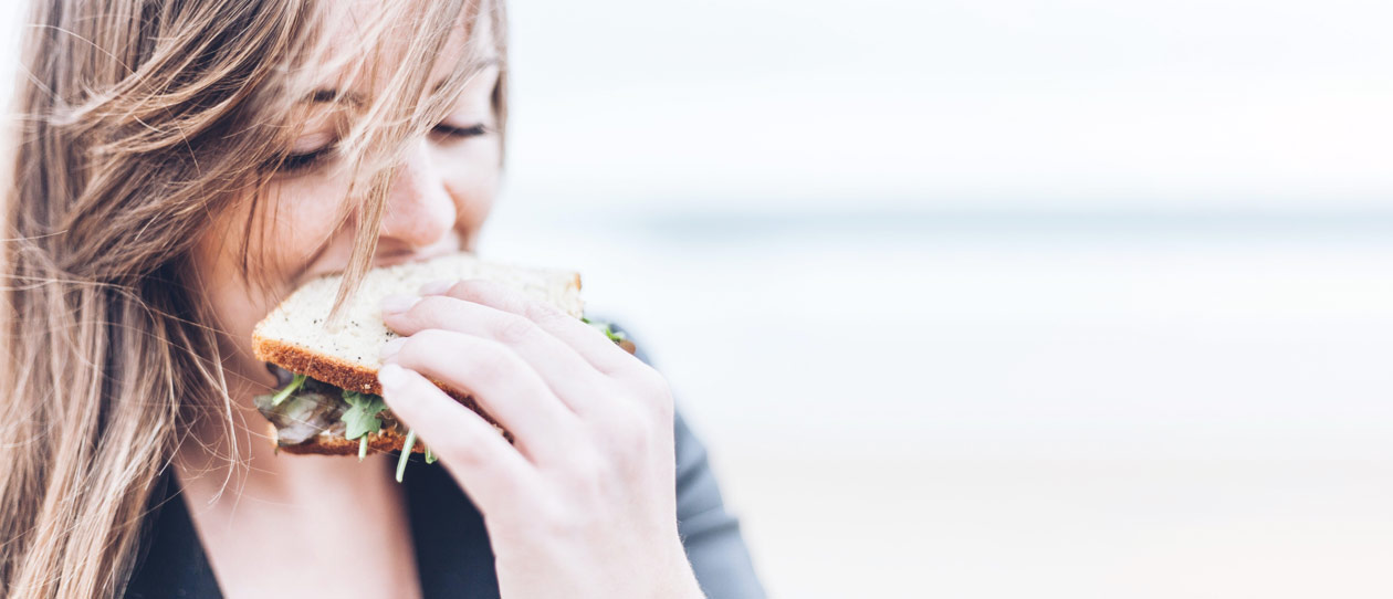 Up close image of a young woman eating a sandwich