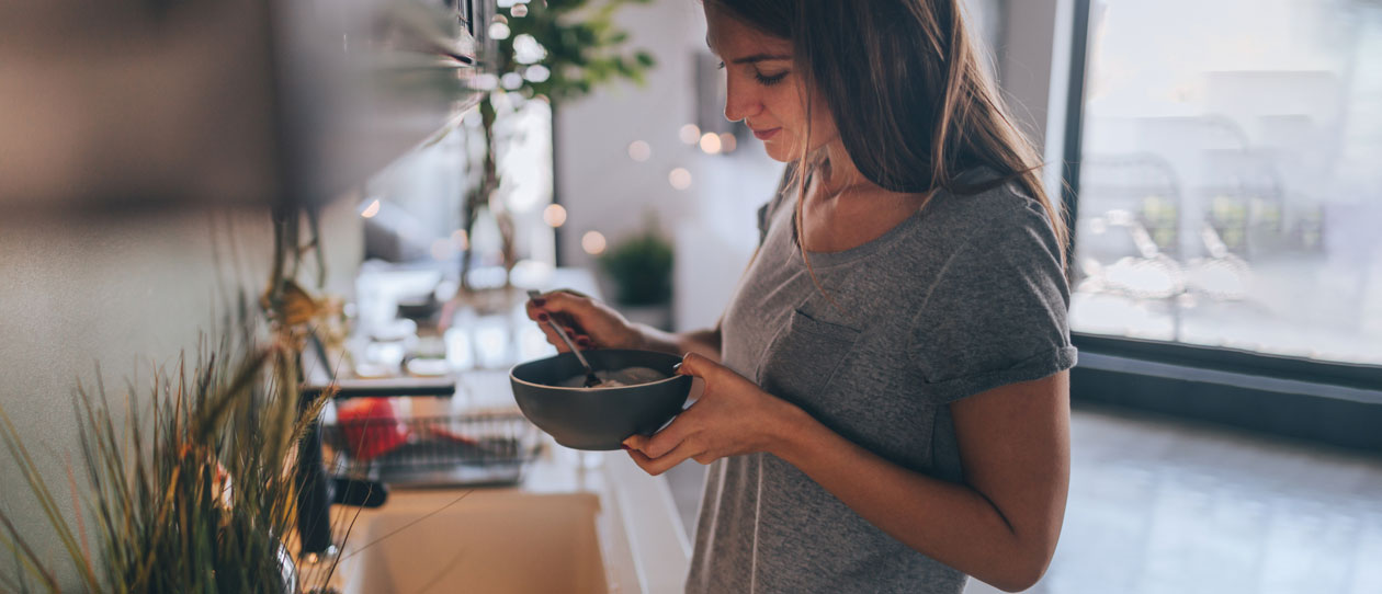 Woman eating a bowl of cereal for breakfast in the kitchen