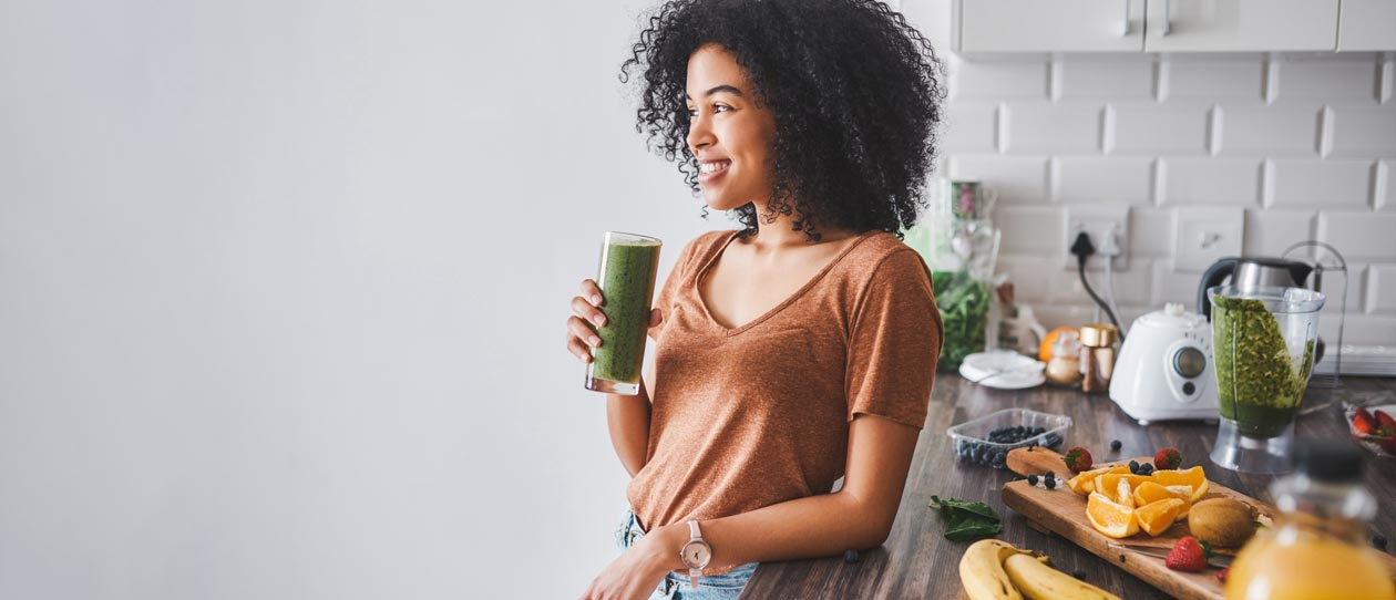 Woman leaning against the kitchen counter drinking a green smoothie