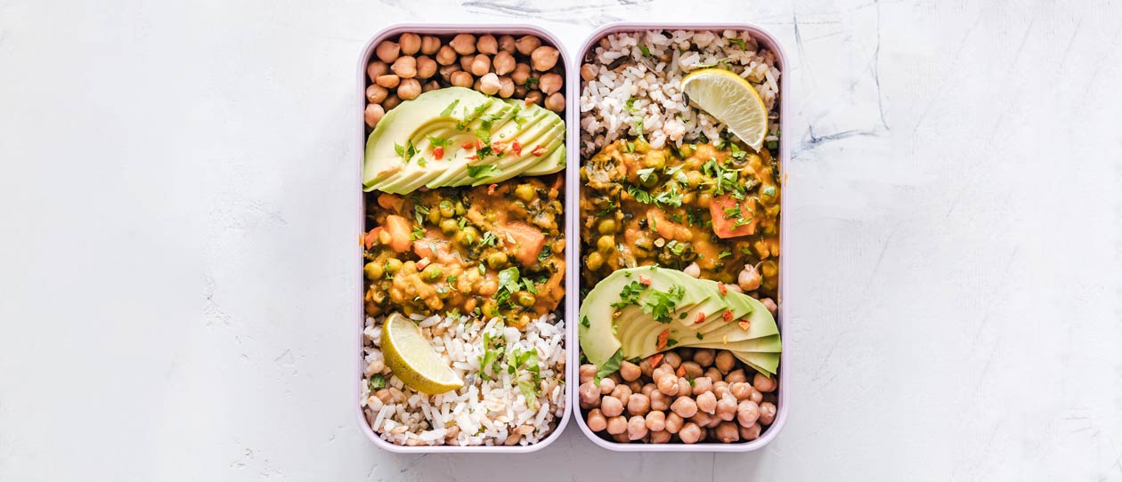 Two lunch boxes side by side with rice, lentils and chickpeas