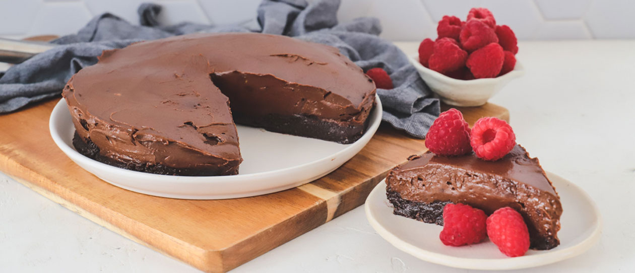 Chocolate avocado and almond mousse cake with fresh raspberries on a white plate