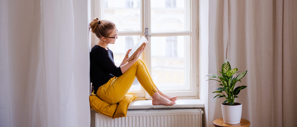 Young woman sitting in a sunlit windowsill reading a book