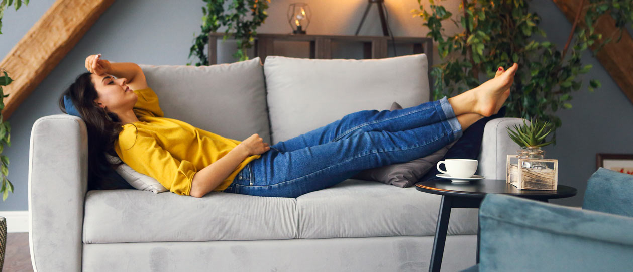 Woman relaxing on the couch at home with a cup of tea