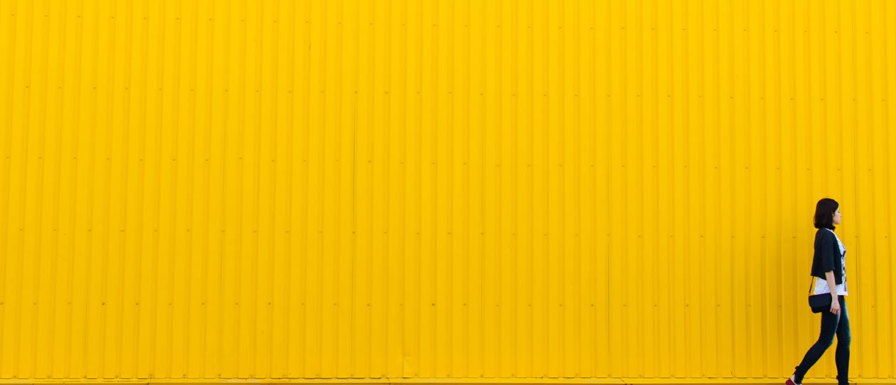 Young woman walking in front of a yellow wall